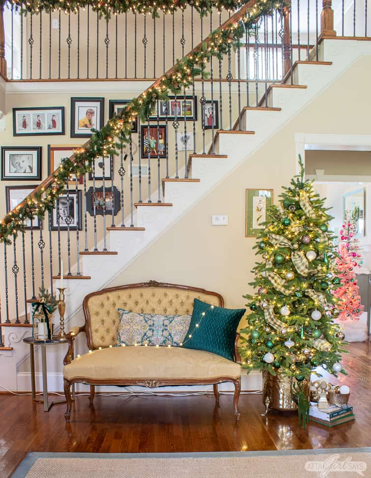 Christmas tree in a brass planter beside a tufted back yellow French settee