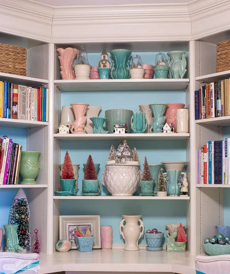 built in bookcases painted aqua and white decorated with vintage pastel McCoy pottery for Christmas