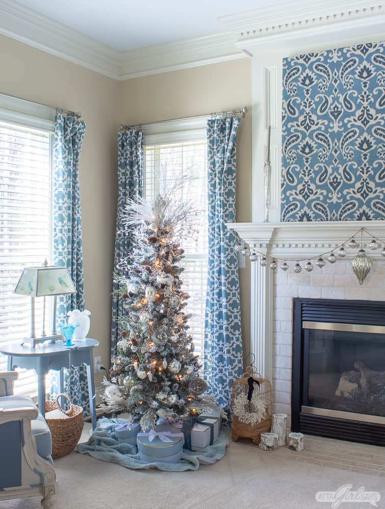 flocked Christmas tree beside a fireplace in a bedroom