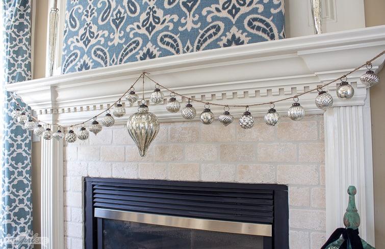 mercury glass ornament garland on a mantel