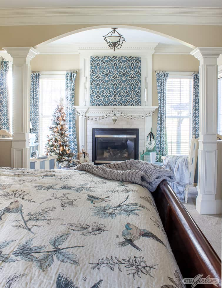 master bedroom with a fireplace decorated in blue and white for Christma
