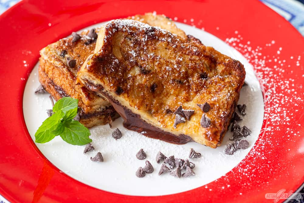 two half slices of grilled Nutella stuffed toast on a plate with chocolate chips and mint leaves