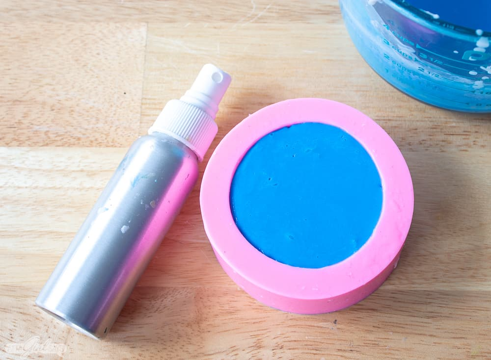 pink soap mold filled with blue melt and pour soap with a metal spray bottle