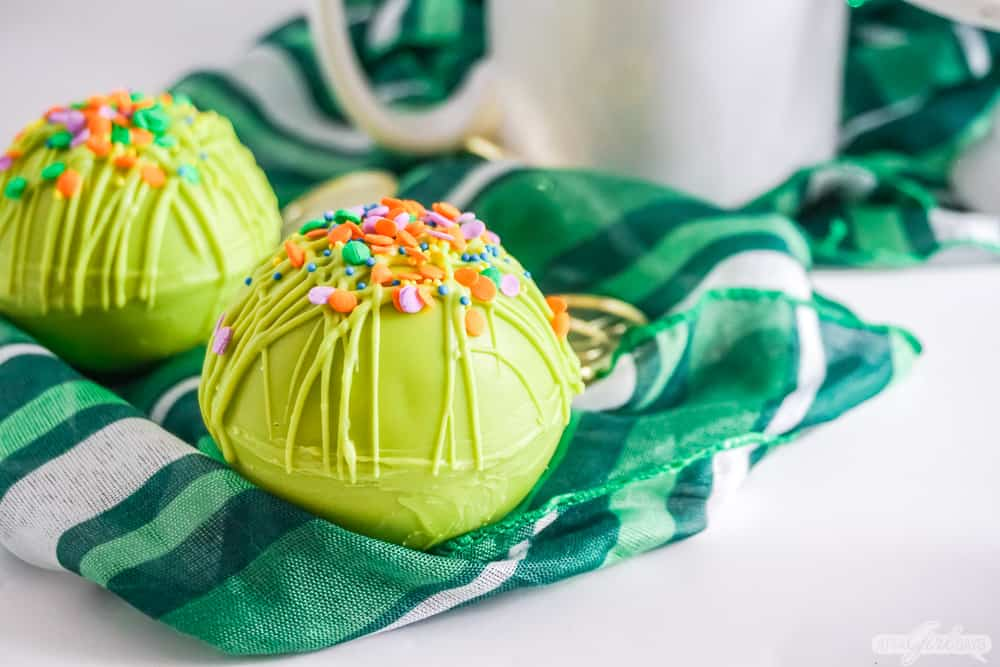 green hot chocolate bomb with rainbow sprinkles on a plaid scarf