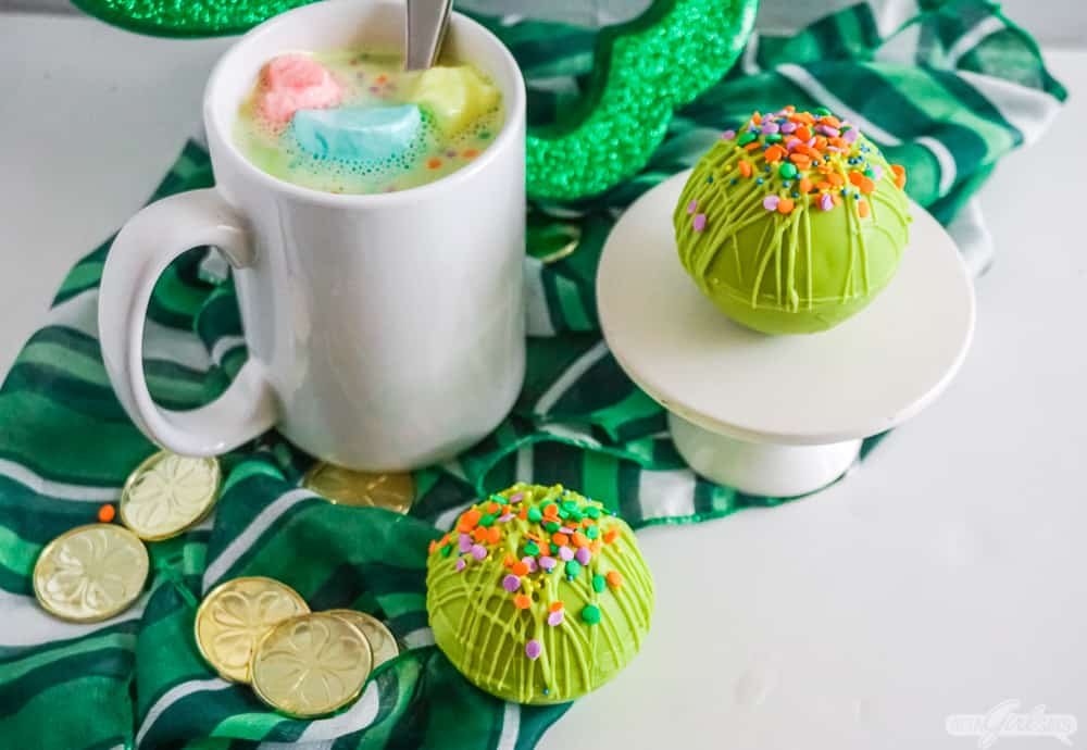 mug of St. Patrick's Day green hot chocolate with green rainbow hot cocoa bombs