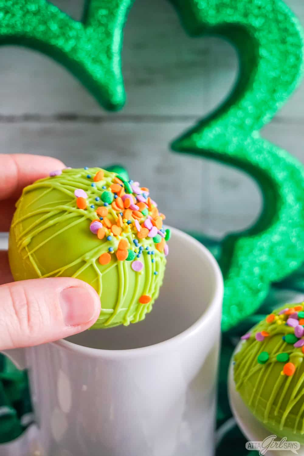 hand placing a St. Patrick's Day hot cocoa bomb in a white mug