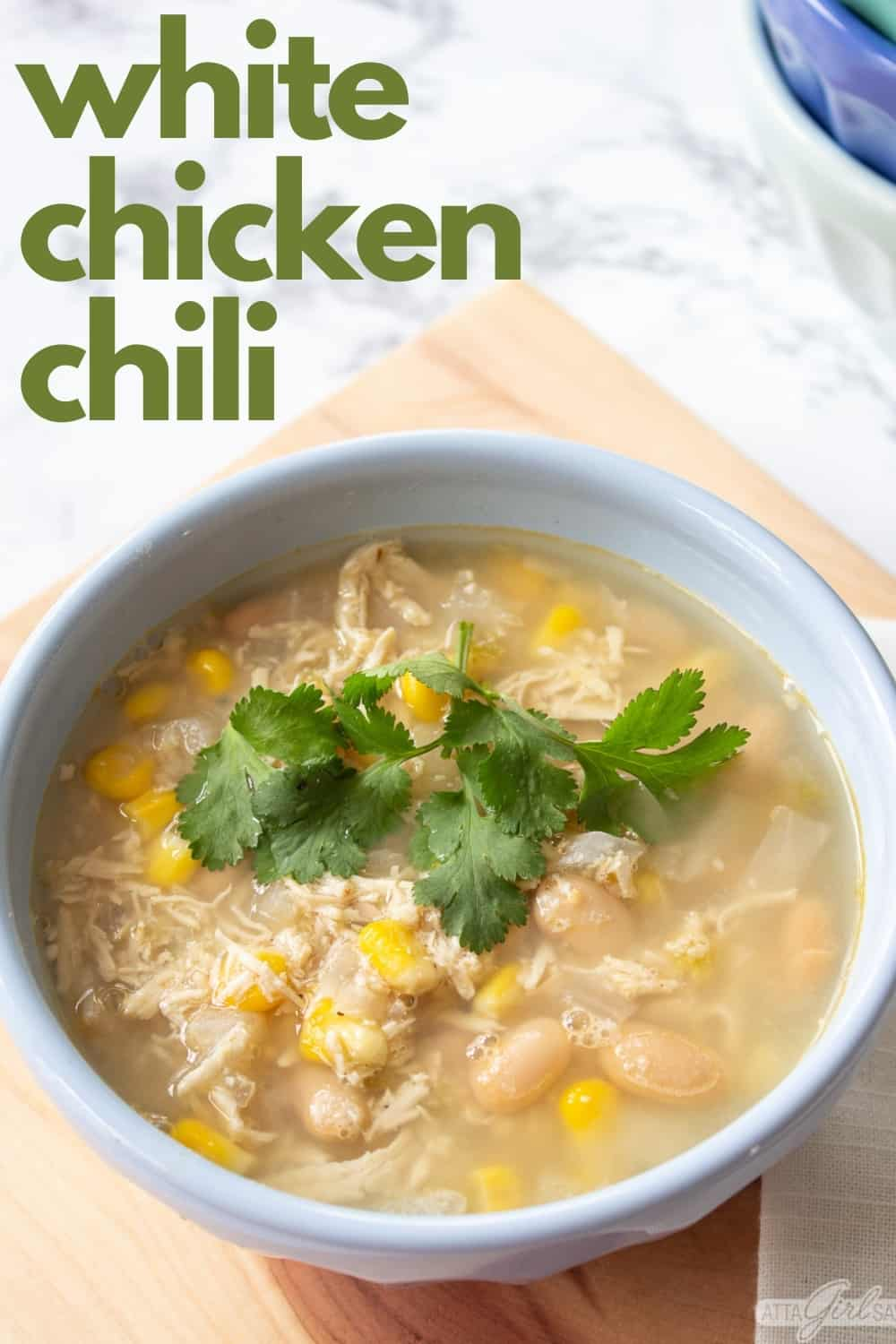 bowl of slow cooker white chicken chili on a wood board