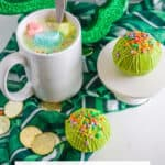 hot cocoa in a mug with Lucky Charms marshmallows with green hot cocoa bombs