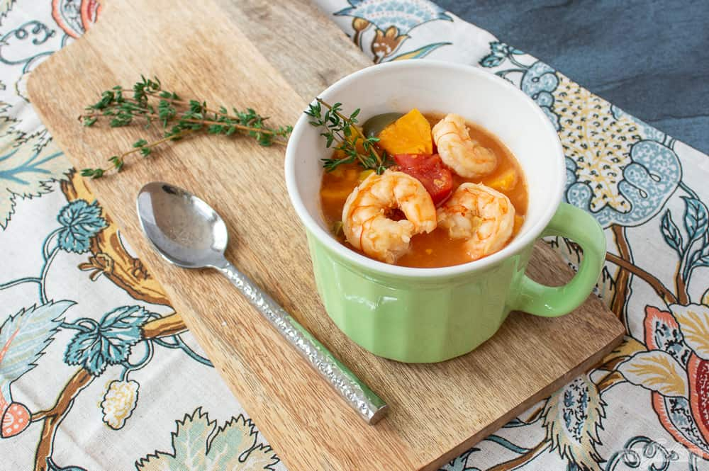 bowl of shrimp soup on a wooden board on a floral print napkin
