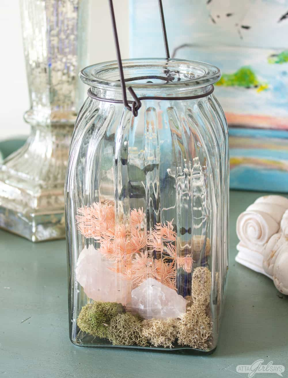 glass jar filled with homemade potpourri made from dried flowers, rocks and moss