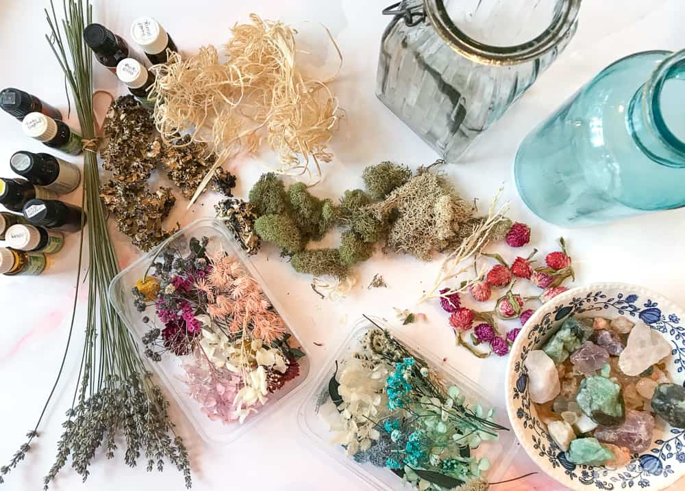 dried forals, herbs, moss and gemstones on a marble counter