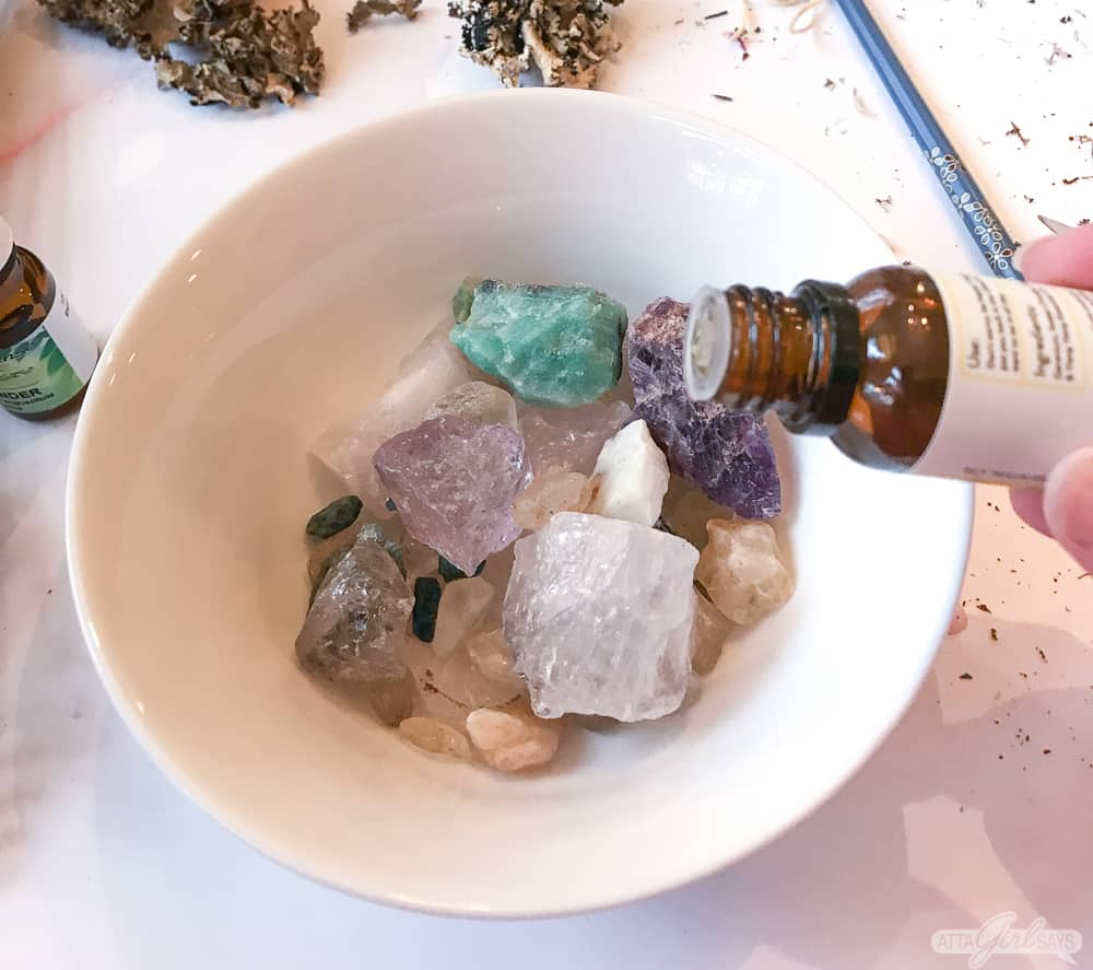 adding essential oil fragrance to gemstone rocks in a bowl to make homemade potpourri