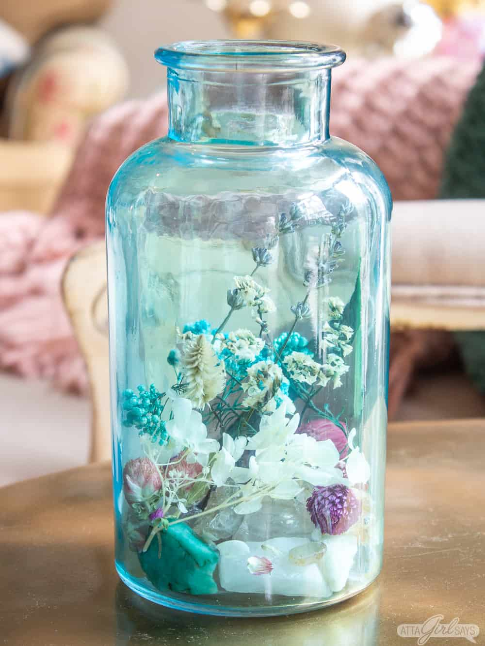 aqua blue glass jar filled with dried florals and gemstone rocks homemade potpourri