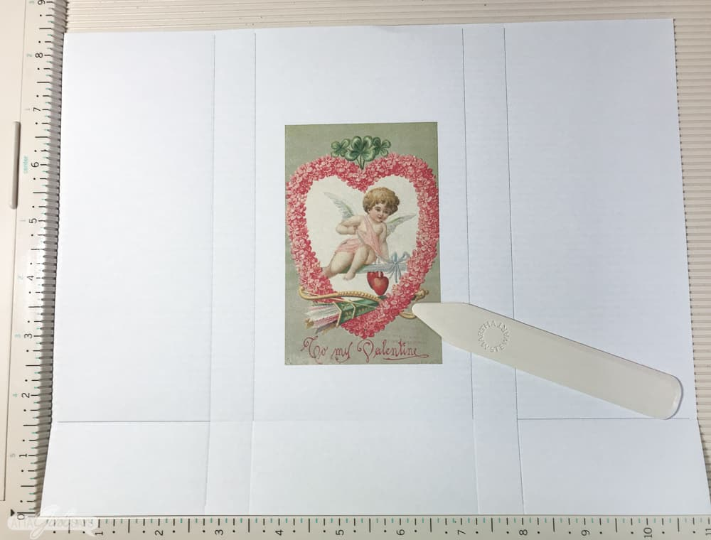 vintage valentines day postcard image on a scoring board with a bone folder