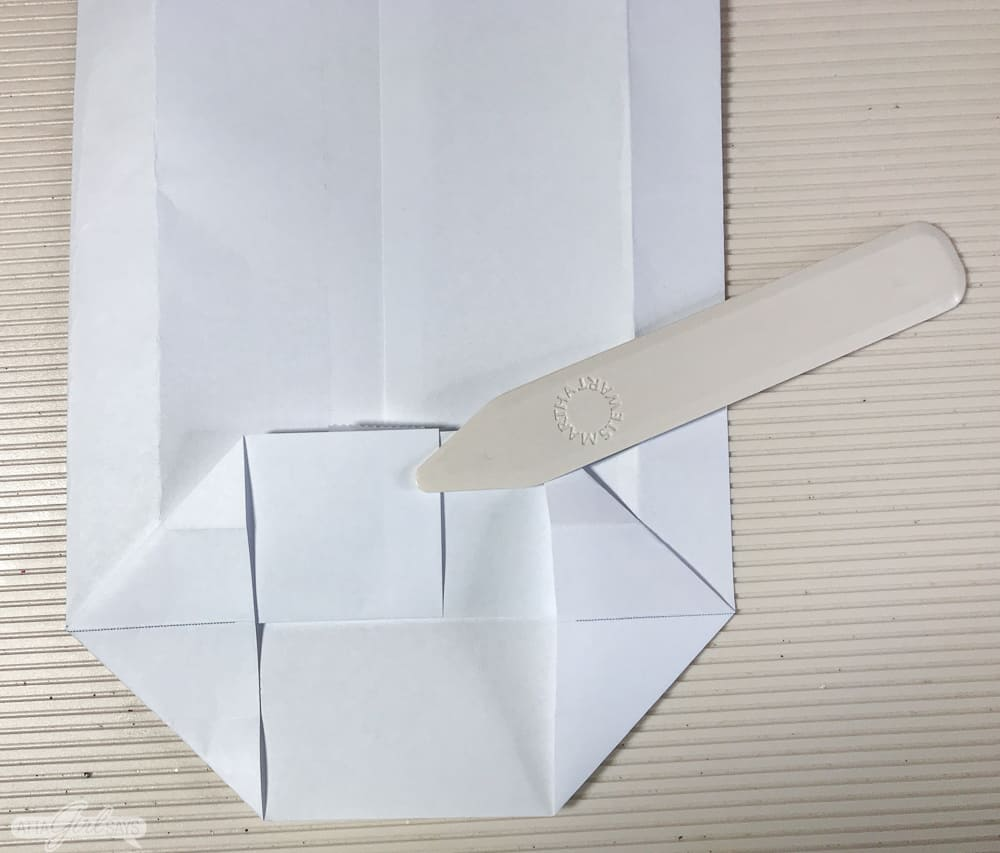 folding a sheet of paper into a bag with a bone folder