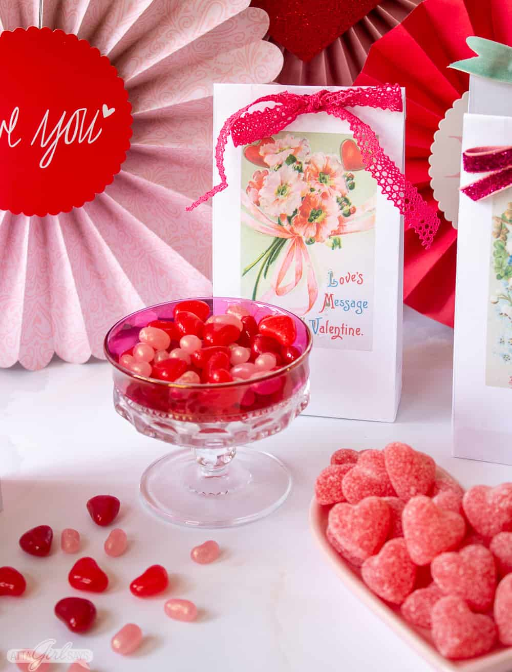 vintage candy dish filled with heart shaped jelly beans with a Valentine's Day treat bag in the background