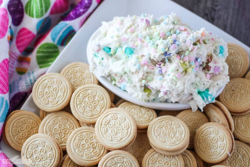Bowl of Easter funfetti dip on a tray with Golden Oreo cookies
