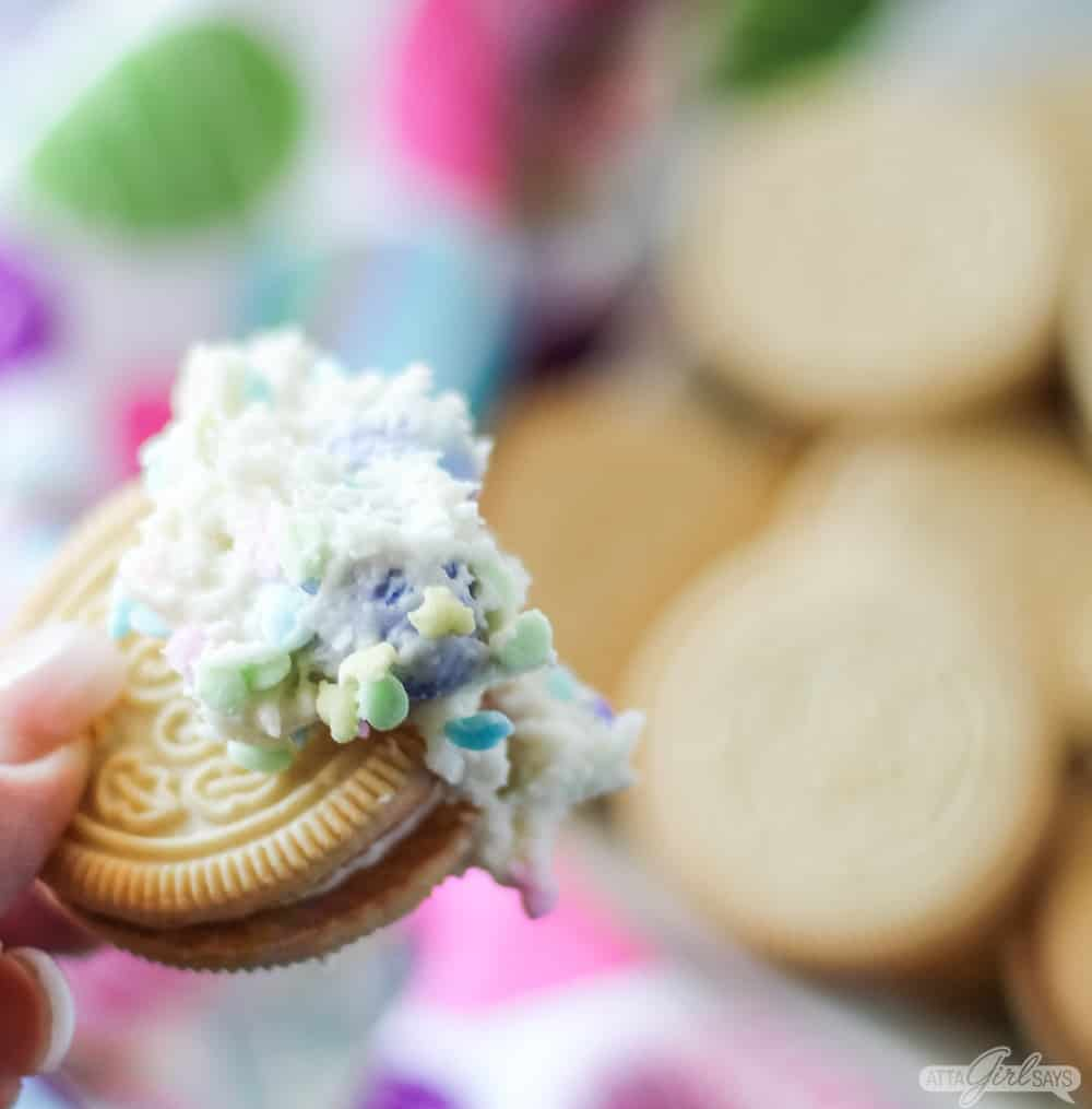 Golden Oreo cookie dipped in frosing with sprinkles