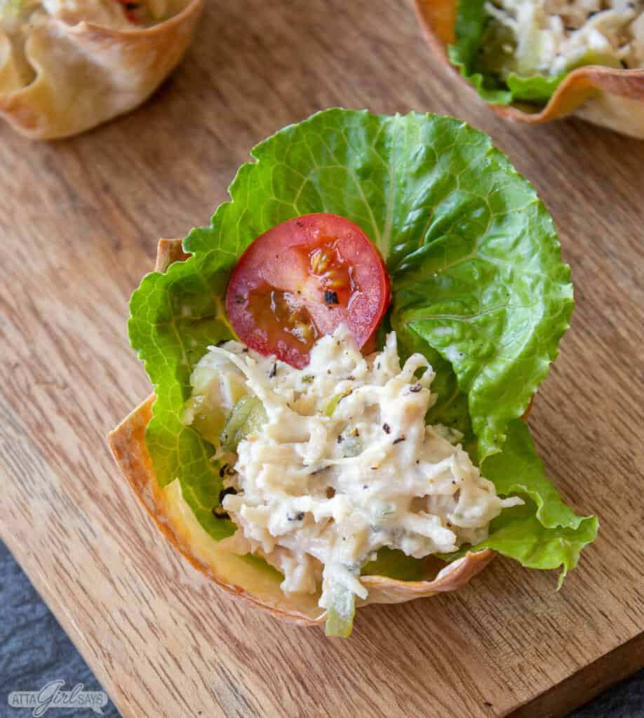 chicken salad garnished with a tomato slice on a bed of lettuce in a wonton cup