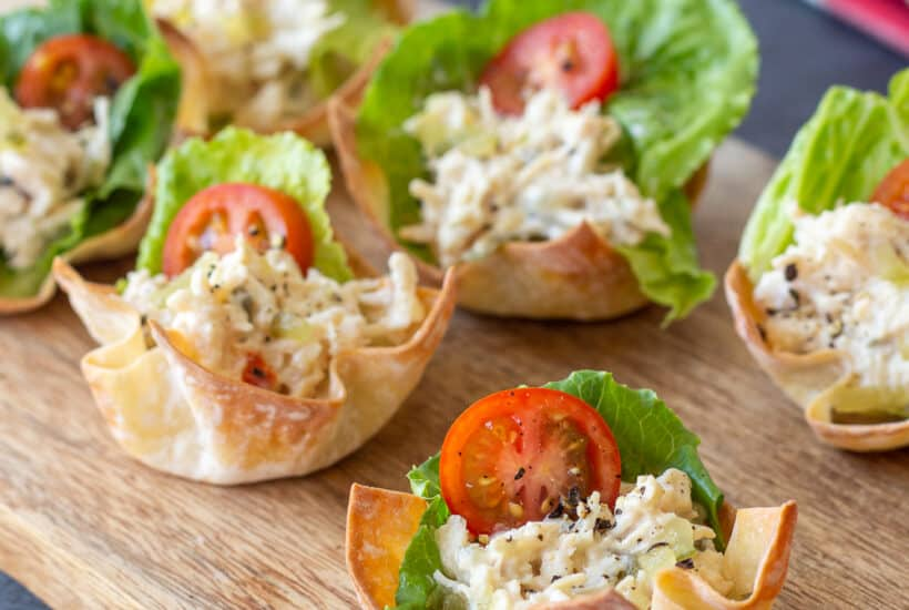 chicken salad wonton cups with lettuce and tomato on a wooden board