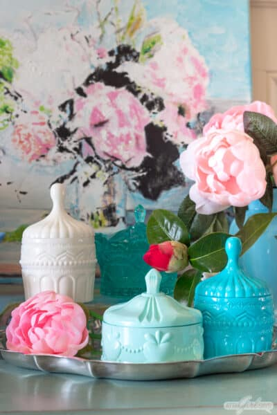 colorful pastel resin trinket boxes on a silver tray with a peony painting and vintage Fenton glass vases