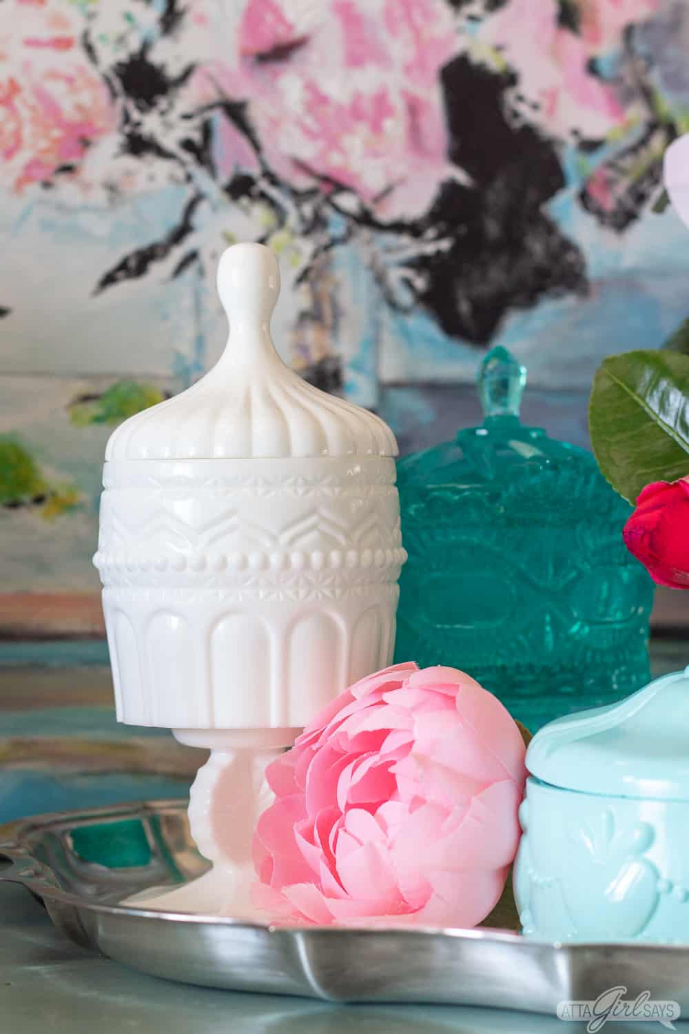 white resin jar on a pedestal with peony flowers and other colorful resin pieces