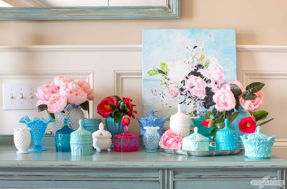 collection of colorful milk glass and faux vintage milk glass pieces on a painted buffet