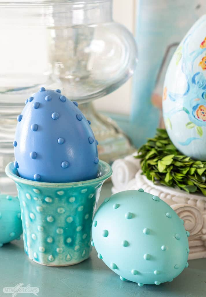 blue hobnail Easter egg in an aqua vintage McCoy planter with a green egg beside it