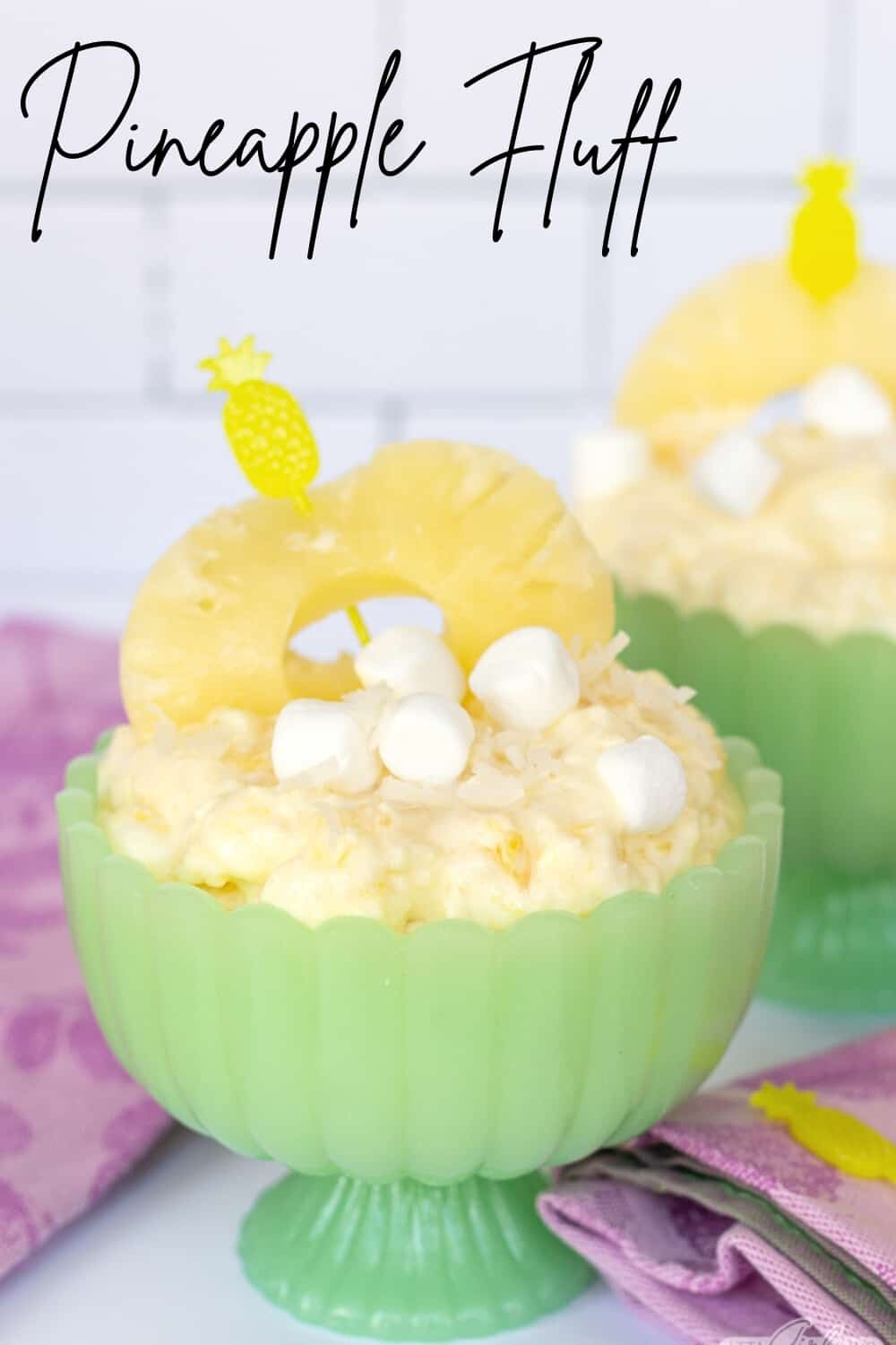 pineapple fluff garnished with marshmallows and pineapple ring in a green jadeite compote bowl
