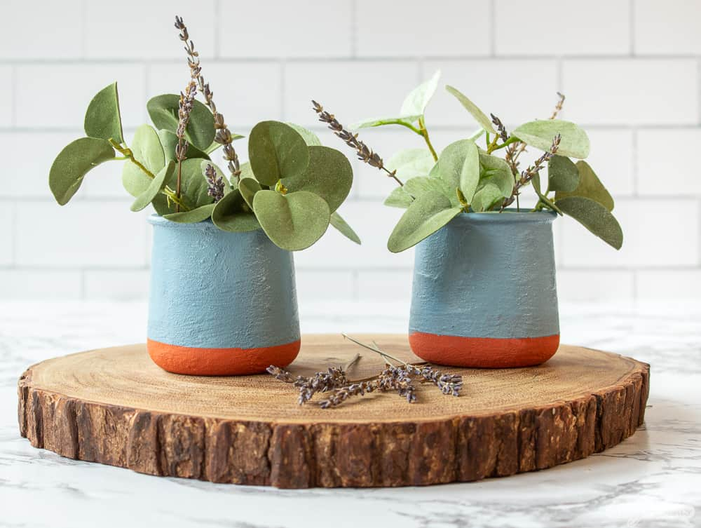 two French yogurt jars with eucalyptus and lavender on a wooden charger