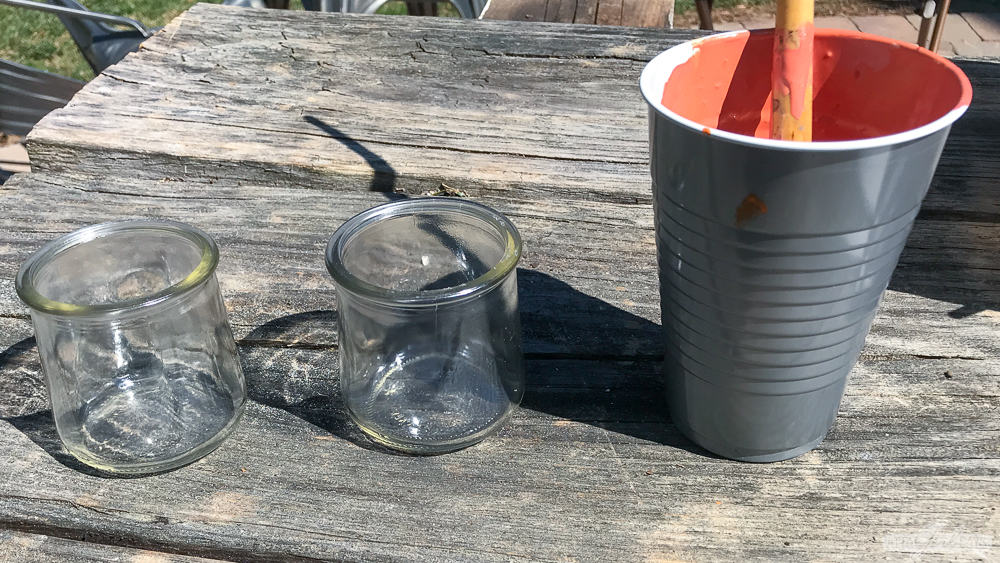 glass yogurt jar beside a cup of terracotta paint