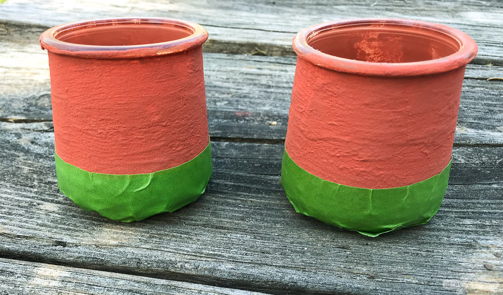 terracotta painted jars with green masking tape on the bottom