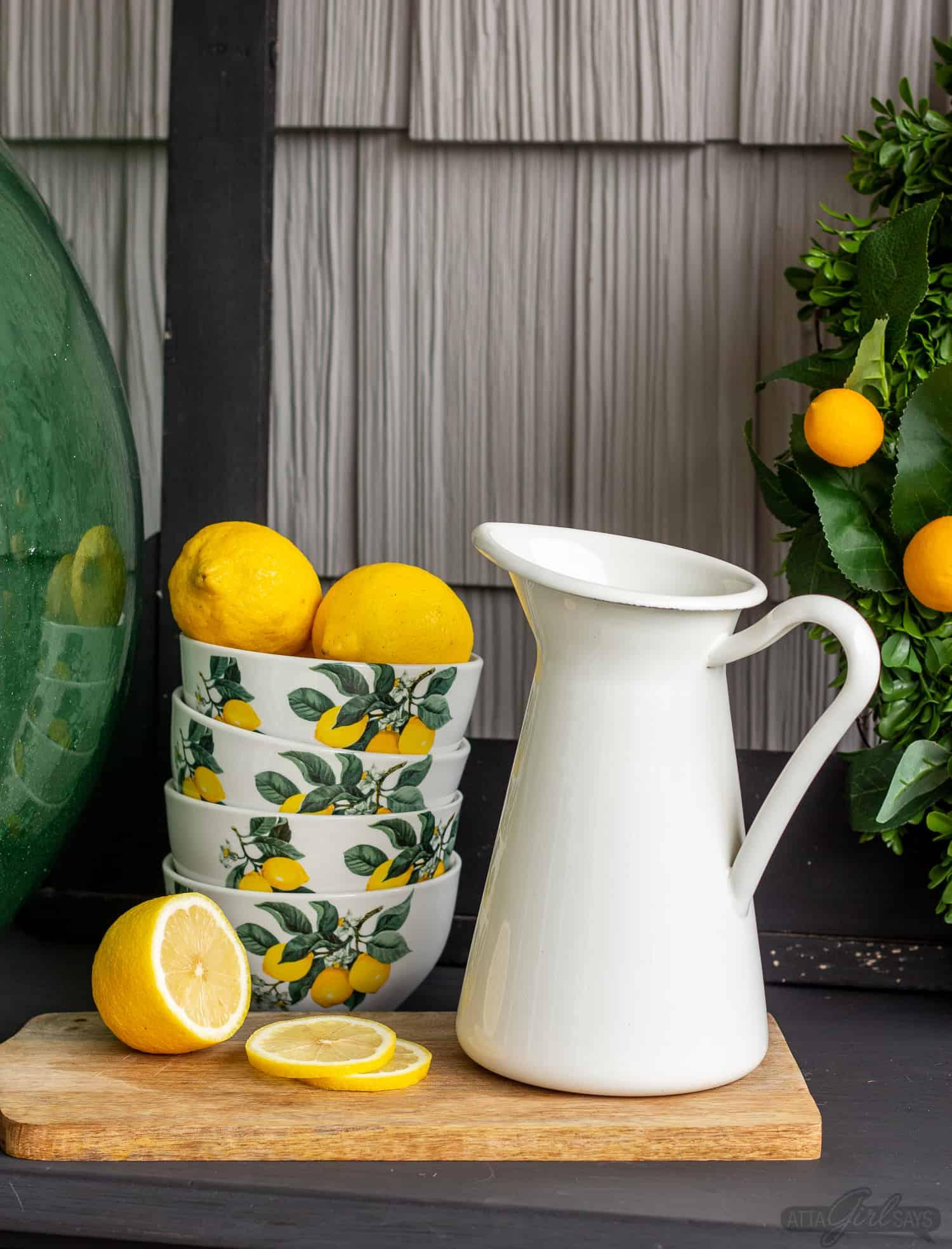 lemon bowls beside a white farmhouse pitcher as part of summer porch decor
