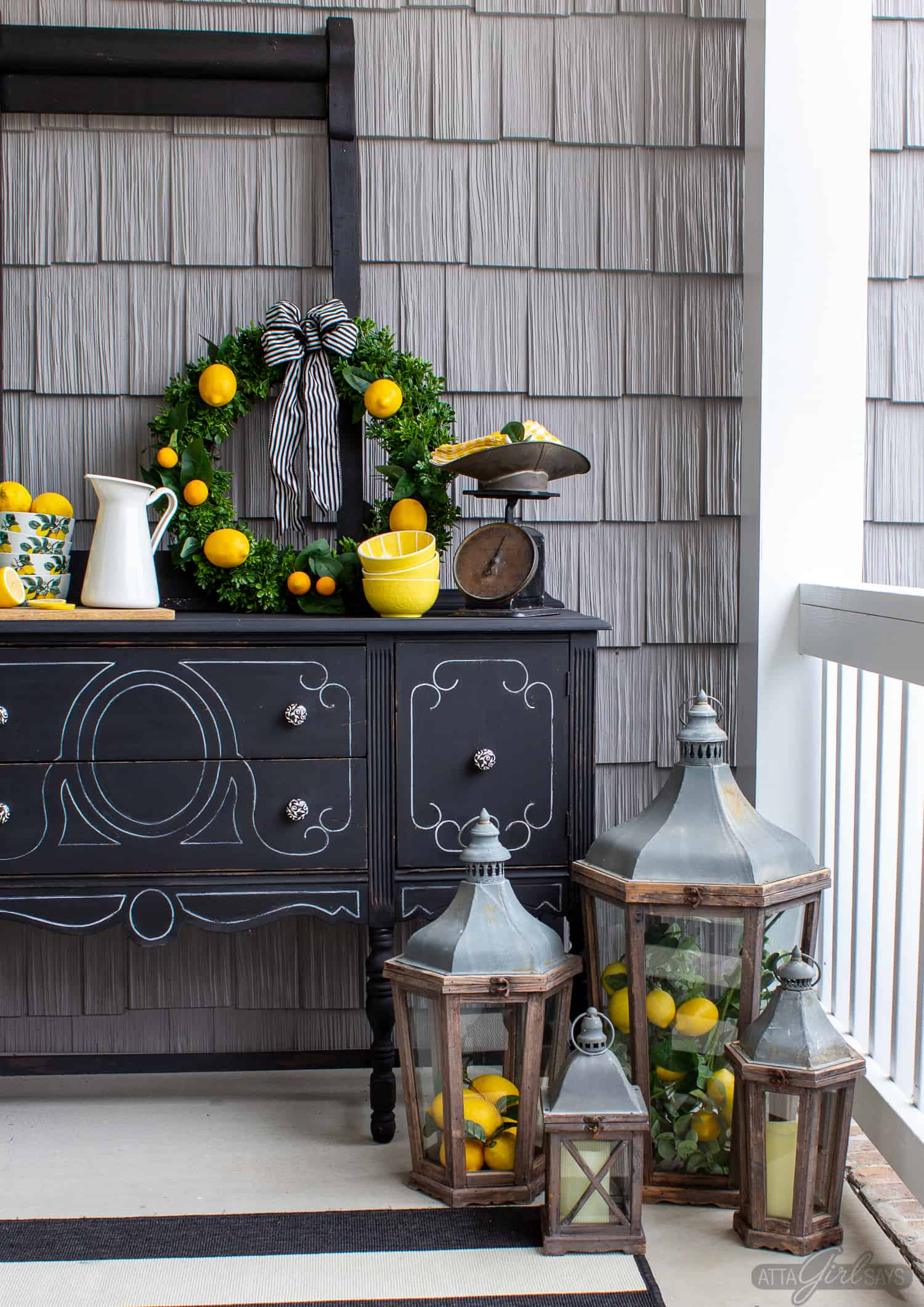 black painted buffet server on a front porch decorated with lemon yellow accents