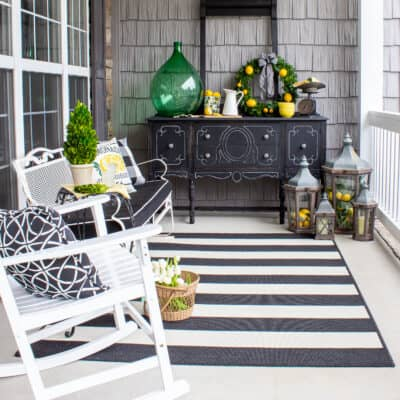summer front porch decorated with black and white furniture and lemon yellow and green accents