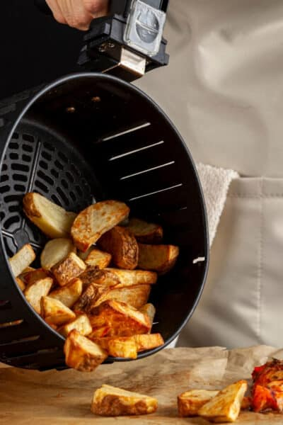 woman in apron pouring home fries out o an air fryer basket