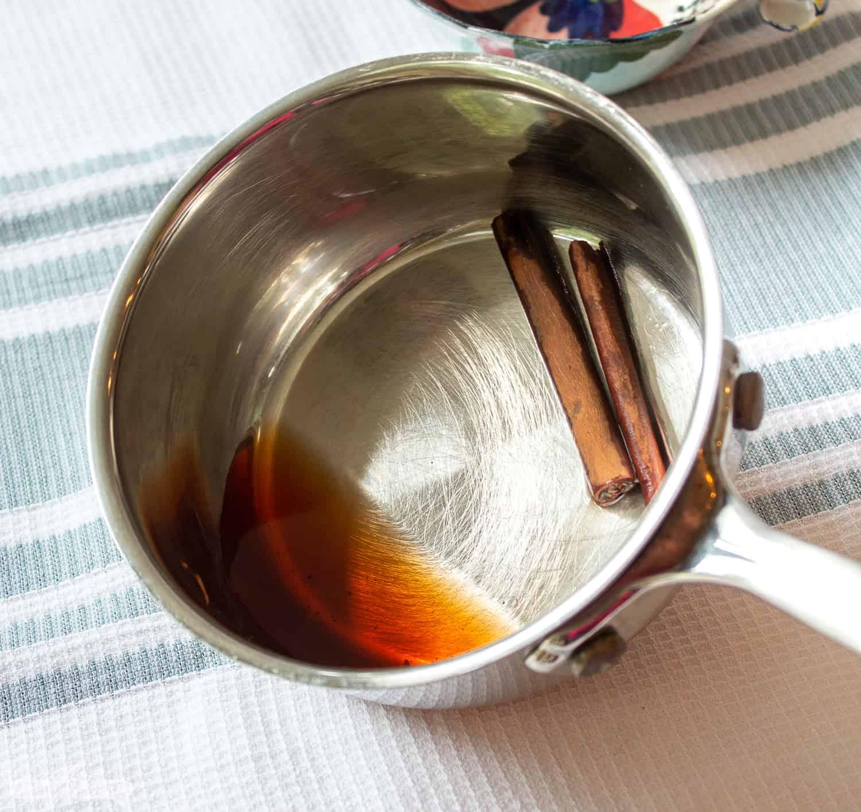 cinnamon infused water and cinnamon sticks in a saucepan