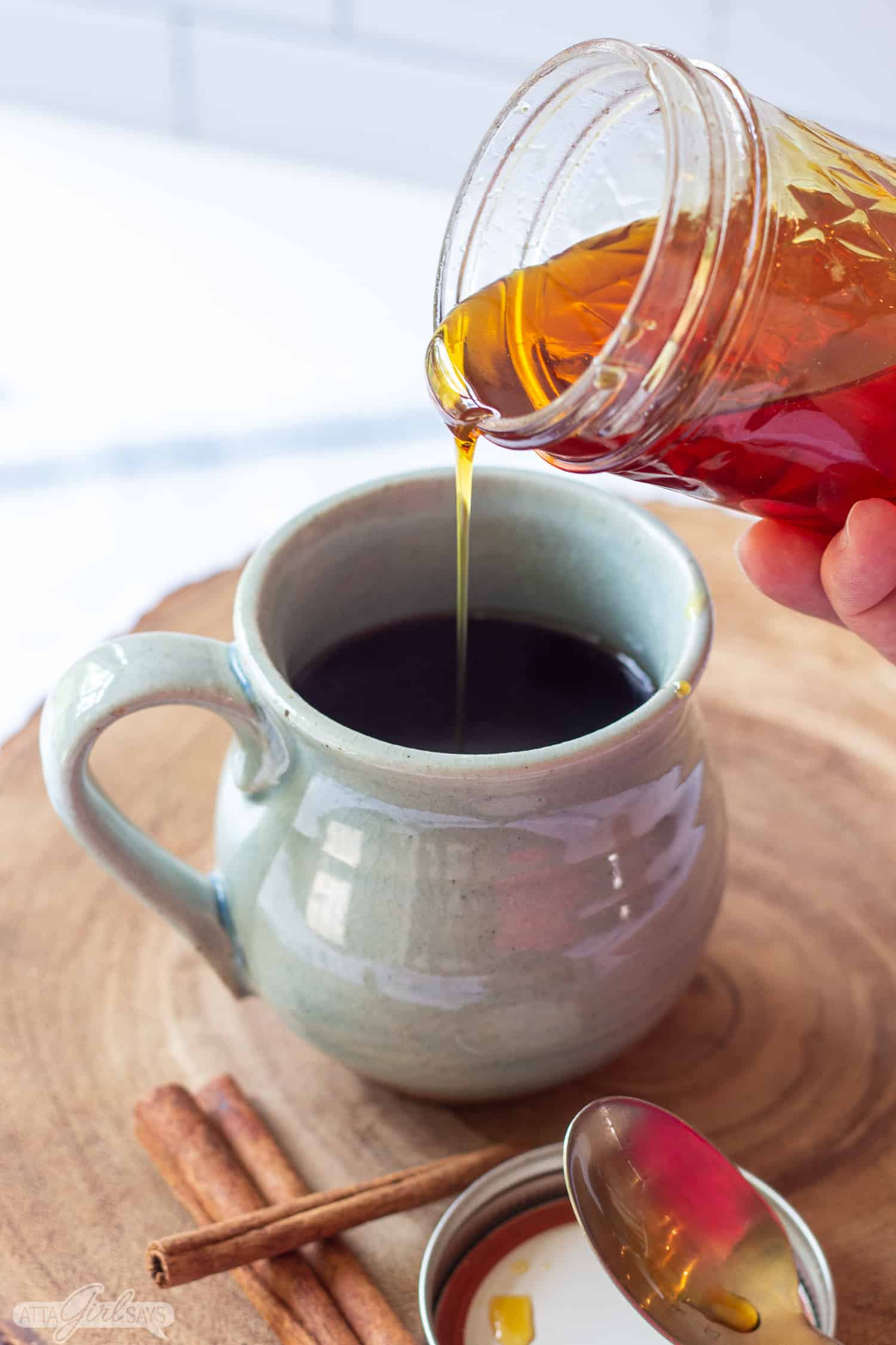 pouring syrup from a jar into a coffee mug