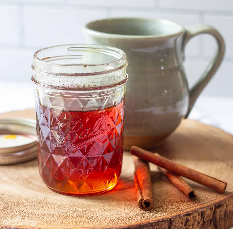 jar of cinnamon caramel simple syrup with a coffee mug and cinnamon sticks