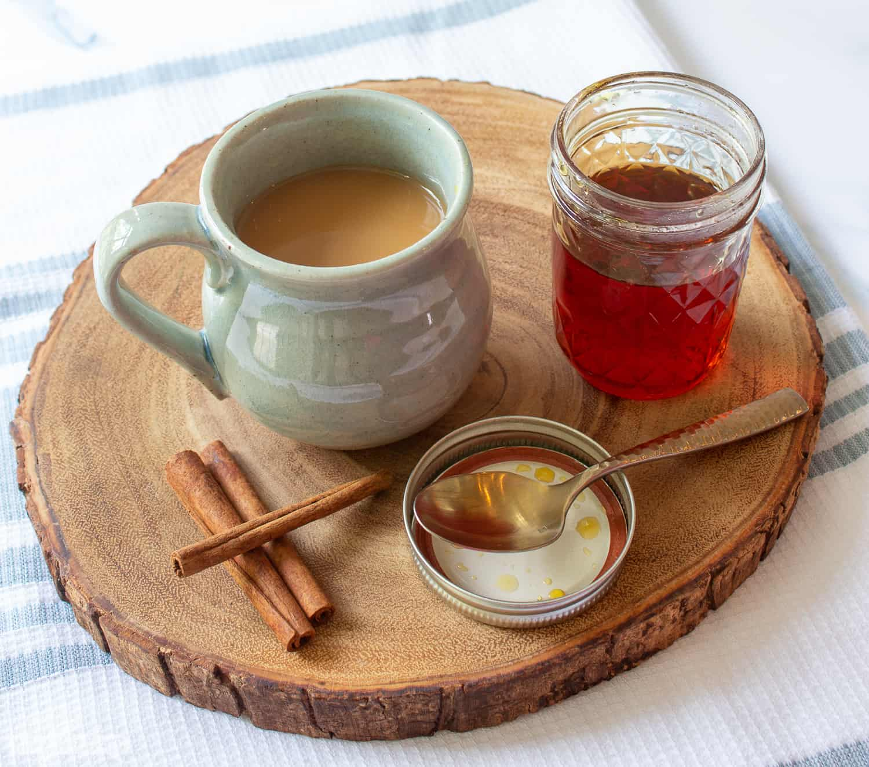 coffee mug, caramel syrup, cinnamon sticks on a wooden board
