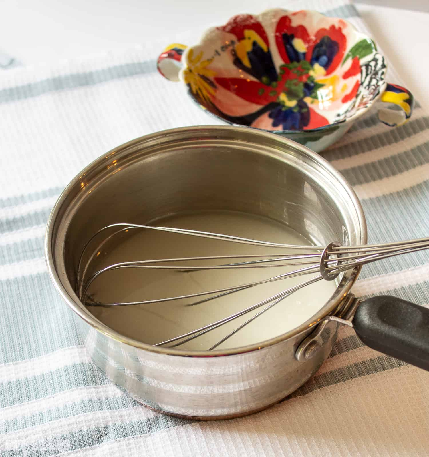 sugar and water in a saucepan with a whisk