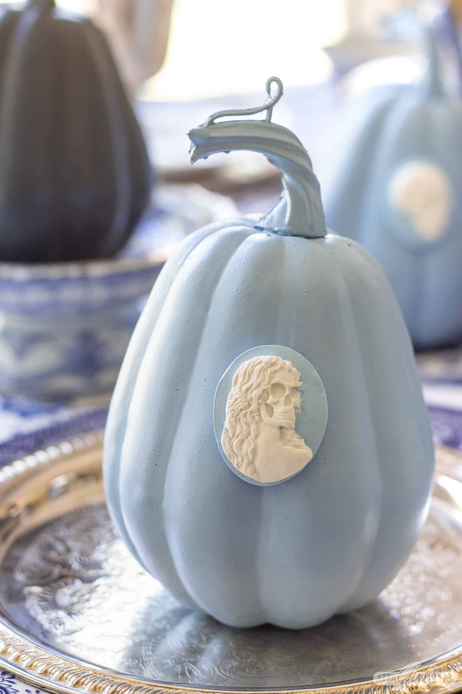blue and white Wedgwood jasperware inspired pumpkin with a skeleton cameo attached to it