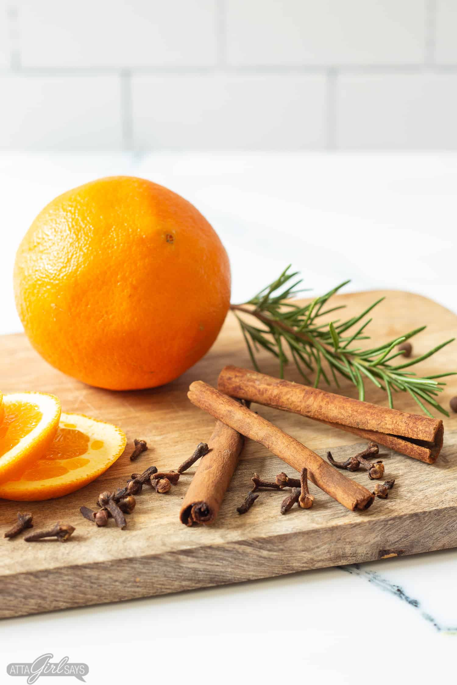oranges, cinnamon sticks, spices and rosemary on a cutting board