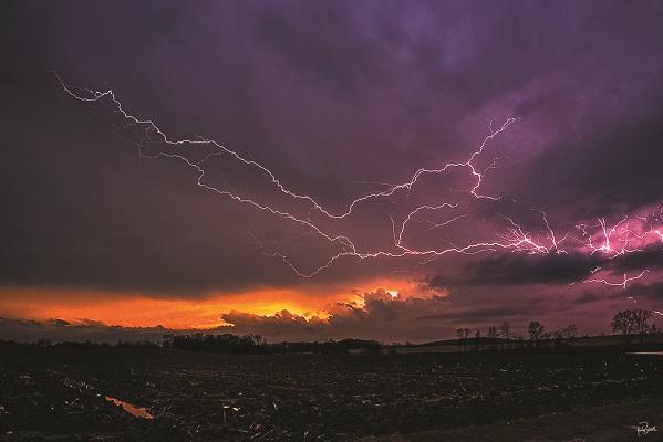 Lightning at sunset across rural Wisconsin farmland