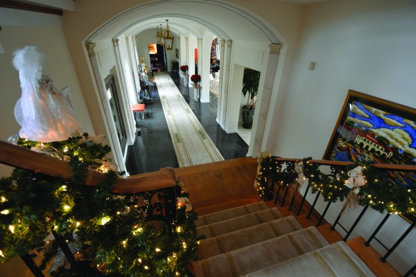 ALTA VISTA: The bannister is wrapped with garland accented  with off-white and gold decorations.