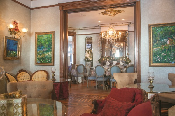 Furniture in the music room includes pieces that represent the period when the house was completed in 1885, including Eastlake styles featuring rich, red velvet upholstery. Paintings in the impressionist style by local artist Weston Courier flank the large entryway to the dining room.