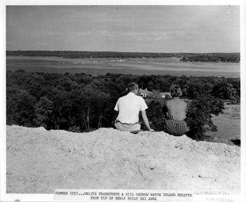 In the summer of 1957, Bill Grunow, Jr. and Melita Frankfurth sit atop the newly built ski hill, watching a regatta on Geneva Lake below. Bill died on March 5, 2012.