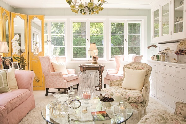 The ladies' lounge is a garden party no matter the season — seashells, pink furnishings and a yellow floral chandelier were all discovered at the Elkhorn Flea Market. A hat collection on the hutch is a nod to Souza's idea first introduced at Baker House, where guests don vintage chapeaus during their stay.