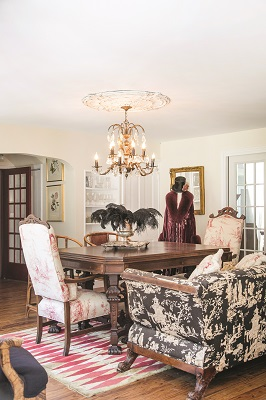 Plush seating takes center stage in the dining room. The 120-year-old high back chairs have been refreshed with new fabric, while the couch shows off its original Chinoiserie patterning. A dazzling 1920s chandelier, a find from Woodstock's Interiors Anew, steals the show.
