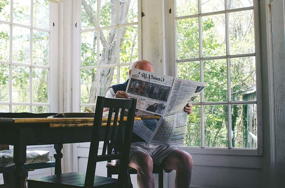 Man reading newspaper image